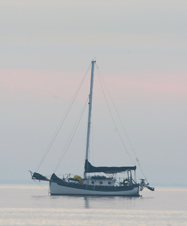 bowsprit: Classic traditional cutter rigged sailboat with bowsprit and outboard stern motor on ocean water at sunrise or sunset