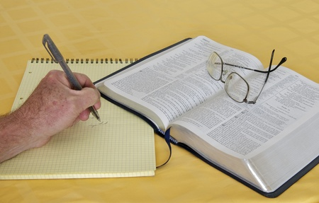 studing: NIV Study Bible with yellow pad, glasses and pen Stock Photo