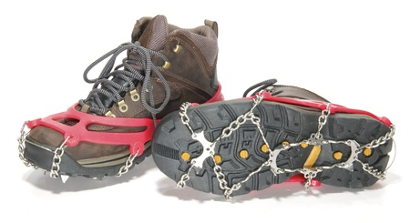 crampons: Hiking Boots with ice cleats or crampons against white background