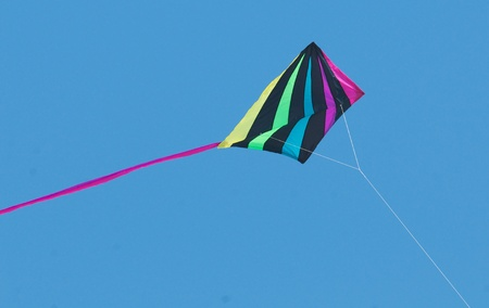 Multicolored kite on string with tail and bright blue sky Stock Photo