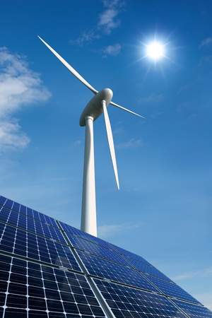 Solar panels and wind turbine against a sunny sky photo