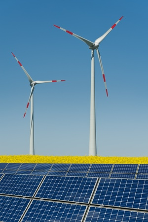monocrystalline: Wind turbines and solar panels in a rapeseed field Stock Photo