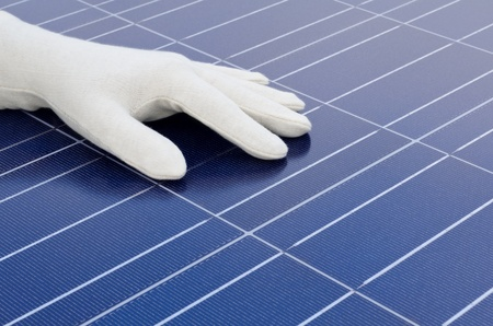 White gloved hand in front of solar cells Stock Photo