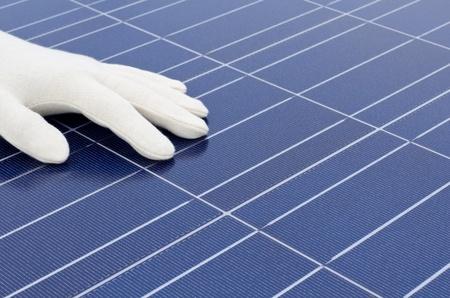 silicio: La mano con guante blanco en la parte frontal de las células solares