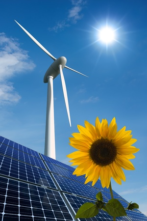 Solar panels, wind turbine and sunflower against a sunny sky Stock Photo