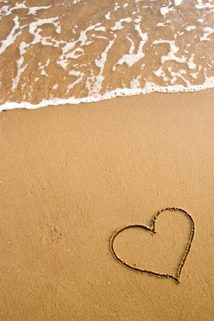 new years vacation: heart simbol on the sand Stock Photo
