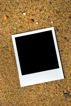 Photo frame on sand background photo