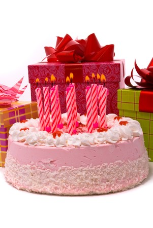Pink pie with eleven candles and gifts in boxes on a white background photo