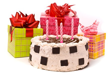 Pie with four candles and gifts in boxes on a white background photo
