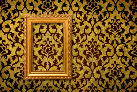 vintage wallpaper: Gold frame on a vintage yellow wall background  Stock Photo