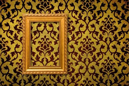 antiek behang: Gouden frame op de achtergrond van een vintage gele wand  Stockfoto