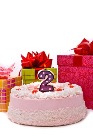 Pink pie with one candle and gifts in boxes on a white background. photo