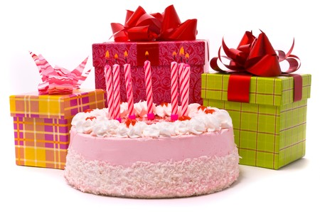 Pink pie with seven candles and gifts in boxes on a white background