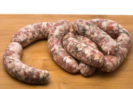 Raw sausages on a chopping board photo