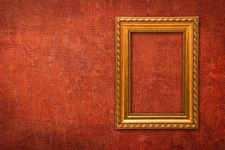 Gold frame on a red wall background Stock Photo - 8236998