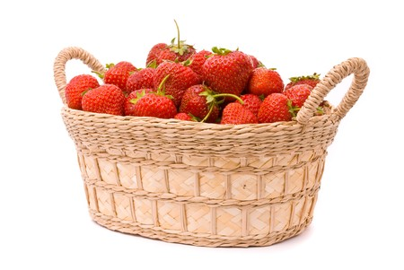 Strawberries in wooden basket isolated on white photo