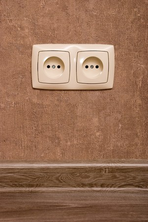grounded plug: Electric socket on brown wallpaper background