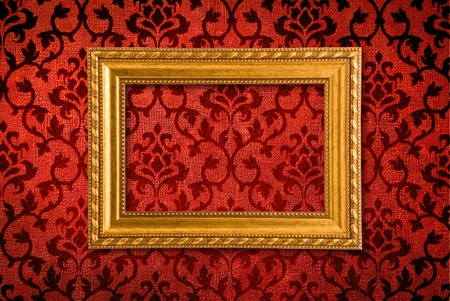 Gold frame on a vintage red wall background  Stock Photo - 8300044