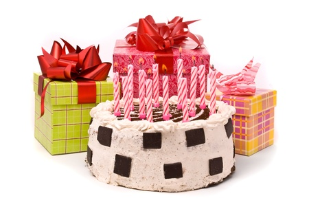 Pie with twelve candles and gifts in boxes on a white background photo