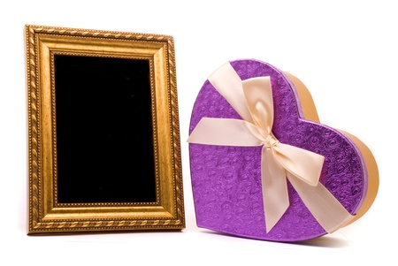 Gold frame and gift box on a white background  photo