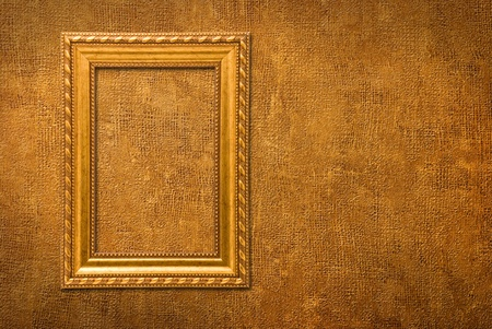 Gold frame on a yellow wall background photo