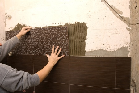 Man tiling a wall in the bathroom photo