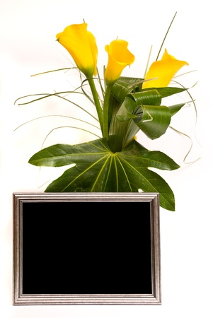 Beautiful bouquet of callas and silver frame on a white photo