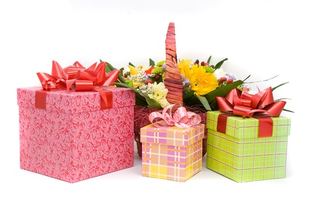 Beautiful bouquet in the basket and present boxes on a white background photo