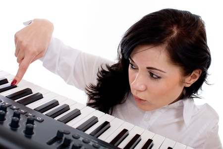 Beautiful young woman playing piano on a white background photo