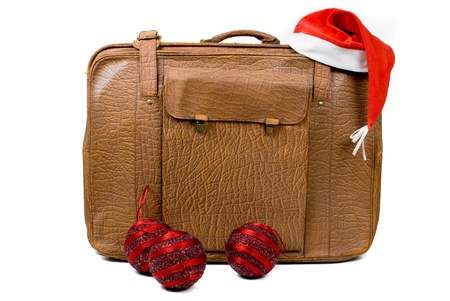 Old suitcase with a Christmas hat and balls isolated on a white background photo