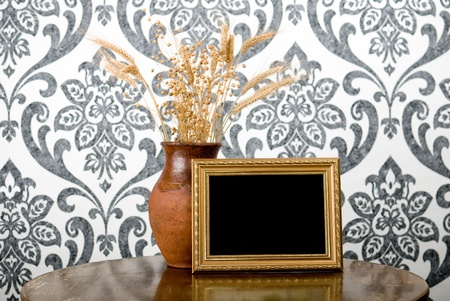 Golden photo frame and jug with wheat and flax on vintage table Stock Photo