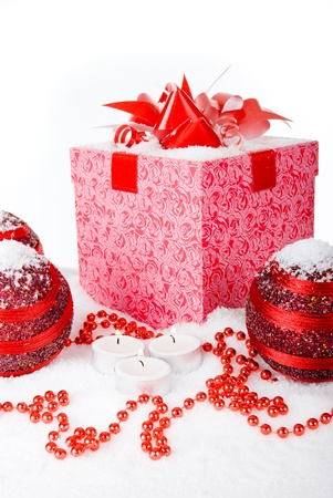 Christmas gift box in the snow with red balls and candles photo