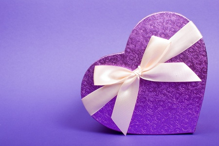 Single heart gift box with ribbon on blue background. Stock Photo