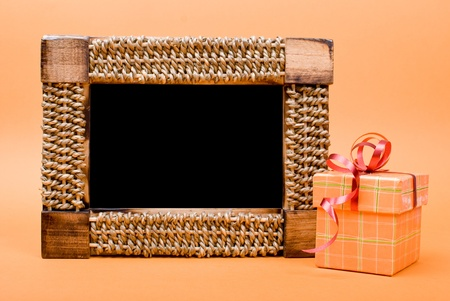 Photo frame and gift box with ribbon on yellow background. photo