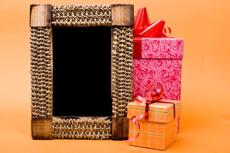 Photo frame and gift box with ribbon on orange background. photo