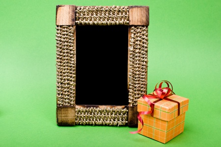Photo frame and gift box with ribbon on green background. photo