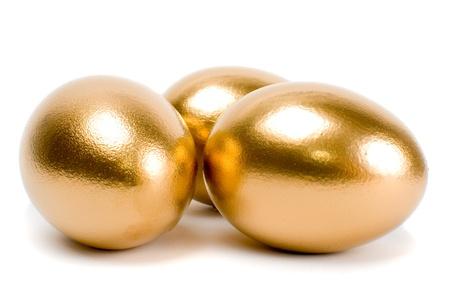 huevos de oro: Huevos de oro. Un s�mbolo de ganar dinero y �xito de la inversi�n en el fondo blanco Foto de archivo