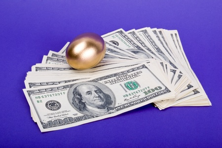 Golden egg. A symbol of making money and successful investment on blue background photo