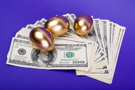 Golden eggs. A symbol of making money and successful investment on blue background photo