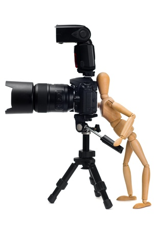 marioneta de madera: La figura de madera de la fot�grafa que fotografi� SLR c�mara en un tr�pode aislado en un fondo blanco