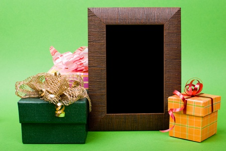Wood photo frame and gift boxes with ribbons on green background. photo