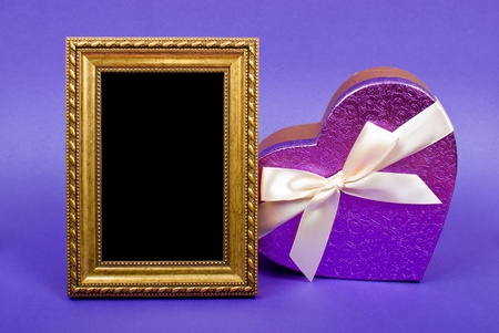 Gold photo frame and heart gift box with ribbon on blue background. photo