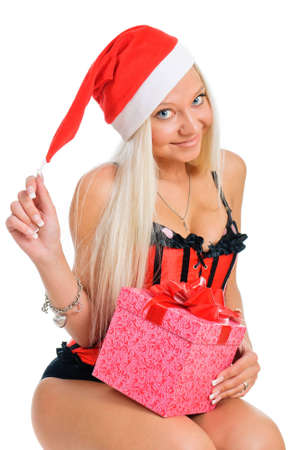 Sexy young blond woman wearing a corset and a Santas hat with Christmas presents on white background photo