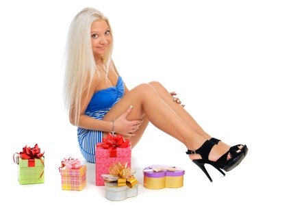 anniversary sexy: Beautiful sexy blond woman in blue dress with present boxes on white background Stock Photo