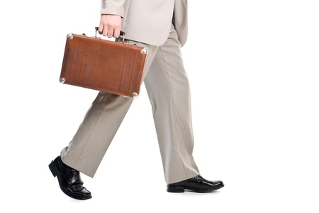 Walking man holding an old suitcase isolated over white background photo