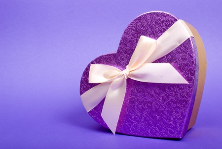 blue gift box: Single heart gift box with ribbon on blue background. Stock Photo