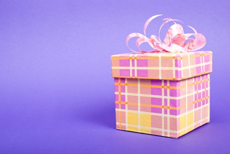Single yellow gift box with pink ribbon on blue background. photo