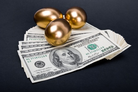 us currency: Golden eggs. A symbol of making money and successful investment on black background