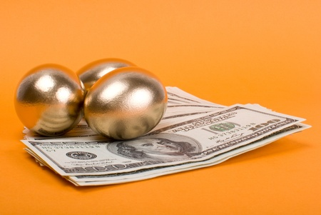 Golden eggs. A symbol of making money and successful investment on orange background photo