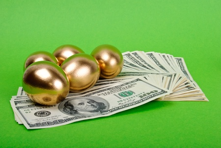 Golden eggs. A symbol of making money and successful investment on green background photo